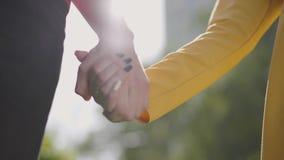 Pares felizes bonitos no amor que anda no parque que guarda delicadamente cada um outro para entregar no dia agradável da mola Cl video estoque