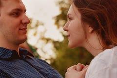 Pares felizes bonitos que olham entre si no parque do verão Imagem de Stock Royalty Free