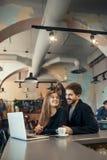 Pares felizes bonitos que trabalham no laptop durante a ruptura de café na barra do café Foto de Stock