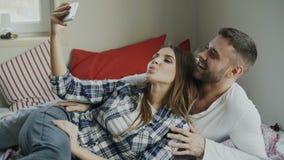 Pares felizes casados que tomam o portrain do selfie ao encontrar-se na cama em casa na manhã video estoque