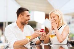 Pares felizes com anel de noivado e vinho no café Imagem de Stock