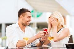 Pares felizes com anel de noivado e vinho no café Fotografia de Stock Royalty Free