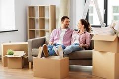 Pares felizes com as caixas que movem-se para a casa nova imagem de stock royalty free