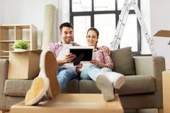 Pares felizes com as caixas que movem-se para a casa nova imagem de stock