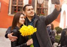 Pares felizes com as flores que fazem o selfie na rua Copie o espa?o imagens de stock