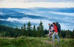 Pares felizes com as trouxas nas montanhas para andar contra o cenário bonito das montanhas fotografia de stock