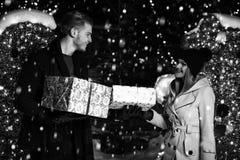 Pares felizes com a caixa de presente sobre luzes de Natal foto de stock