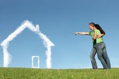 Pares felizes com casa ideal imagem de stock