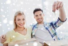 Pares felizes com chave e caixas que movem-se para a casa nova Imagens de Stock Royalty Free