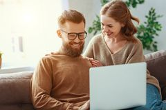 Pares felizes com computador port?til em casa imagem de stock