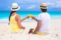 Pares felizes com dois vidros do suco de laranja em uma praia tropical Fotos de Stock Royalty Free