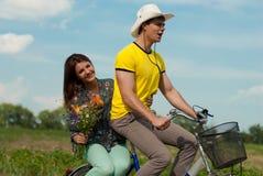 Pares felizes com flores & bicicleta ao ar livre Fotografia de Stock Royalty Free
