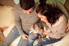 Pares felizes com gato em casa imagens de stock royalty free