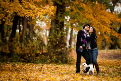 Pares felizes com o cão durante o outono Fotos de Stock