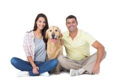 Pares felizes com o cão que senta-se sobre o fundo branco Fotografia de Stock