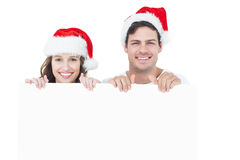 Pares felizes com o chapéu de Santa que guarda um cartaz Imagens de Stock Royalty Free