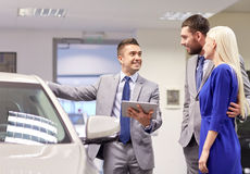 Pares felizes com o concessionário automóvel na feira automóvel ou no salão de beleza Foto de Stock