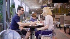 Pares felizes com o filho que passa o tempo junto no terraço exterior que senta-se na tabela Esposa e marido que falam quando men filme