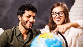 Pares felizes com o globo que escolhe o lugar para o curso imagem de stock royalty free