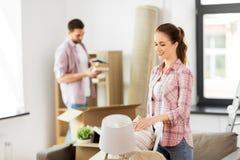 Pares felizes com o material que move-se para a casa nova imagem de stock royalty free