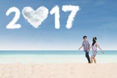 Pares felizes com o 2017 na praia Imagem de Stock