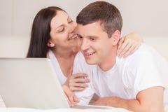 Pares felizes com o portátil no sorriso da cama fotografia de stock royalty free