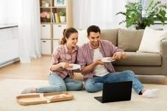 Pares felizes com o portátil que come a pizza em casa imagens de stock