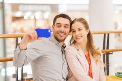 Pares felizes com o smartphone que toma o selfie na alameda Fotografia de Stock