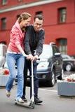 Pares felizes com o 'trotinette' na rua da cidade Fotos de Stock Royalty Free