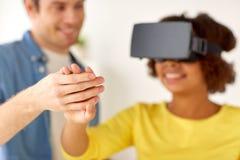Pares felizes com os auriculares da realidade virtual em casa Imagens de Stock