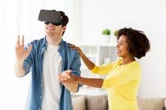 Pares felizes com os auriculares da realidade virtual em casa Imagens de Stock Royalty Free