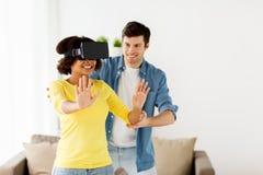 Pares felizes com os auriculares da realidade virtual em casa Fotografia de Stock Royalty Free