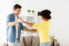 Pares felizes com os auriculares da realidade virtual em casa Foto de Stock