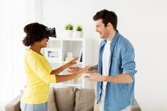 Pares felizes com os auriculares da realidade virtual em casa Fotografia de Stock