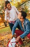 Pares felizes com os cães que jogam fora no parque do outono Imagens de Stock Royalty Free