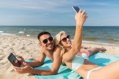 Pares felizes com os dispositivos modernos que encontram-se na praia foto de stock royalty free