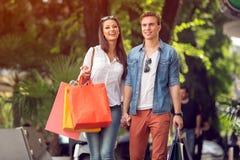 Pares felizes com sacos de compra Fotografia de Stock Royalty Free