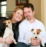 Pares felizes com seus cães imagens de stock royalty free
