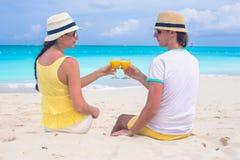 Pares felizes com vidros do suco de laranja sobre Fotografia de Stock Royalty Free