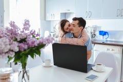 Pares felizes da família usando o portátil ao comer o café na cozinha moderna Homem novo e mulher que abraçam e que beijam fotografia de stock royalty free