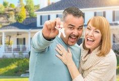 Pares felizes da raça misturada na frente da casa com chaves novas Fotos de Stock