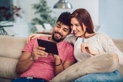 Pares felizes da raça misturada que compram em linha em casa, usando o cartão de crédito foto de stock