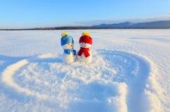 Pares felizes de boneco de neve no amor que está na neve Coração pintado Escritas 2019 Paisagem com montanhas fotos de stock royalty free