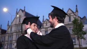 Pares felizes de graduados que olham se video estoque