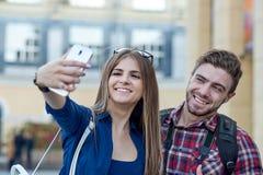 Pares felizes de turistas que tomam o selfie no showplace da cidade foto de stock