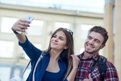 Pares felizes de turistas que tomam o selfie no showplace da cidade imagens de stock