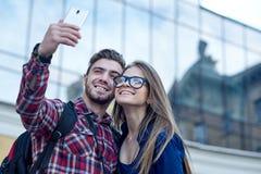 Pares felizes de turistas que tomam o selfie no showplace da cidade fotografia de stock royalty free
