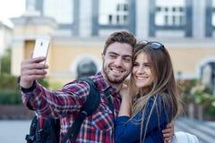 Pares felizes de turistas que tomam o selfie no showplace da cidade Homem e mulher que fazem a foto no fundo da cidade imagem de stock
