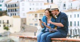 Pares felizes de turistas que tomam selfies com um smartphone vídeos de arquivo
