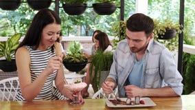 Pares felizes do  de Ð que comem uma sobremesa no café Menina que alimenta seu noivo video estoque